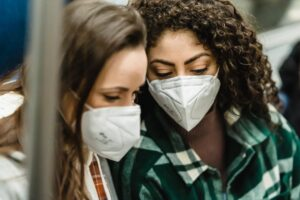 young women in medical masks riding in subway